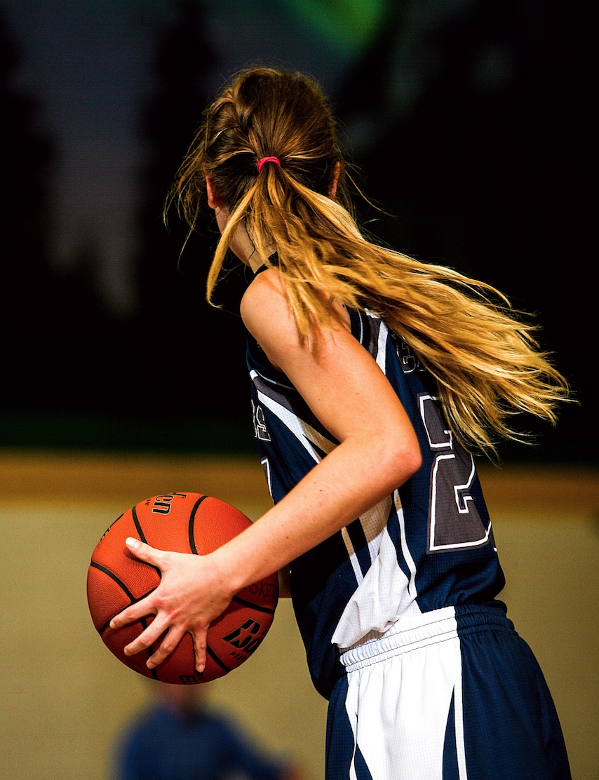 Girl looking to pass basketball in a game